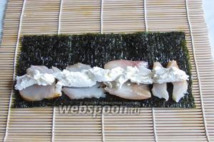 Положить нори блестящей стороной вниз, выложить масляную рыбу ближе к переднему краю нори, сыр выложить на середину рыбы.