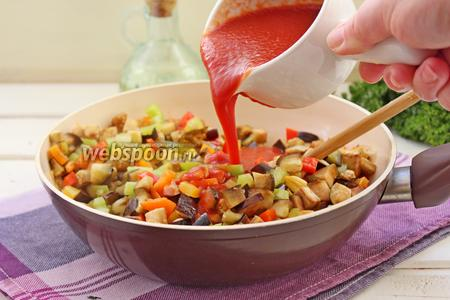 К обжаренным овощами влить томатное пюре, посолить, поперчить, довести до кипения и снять с огня.