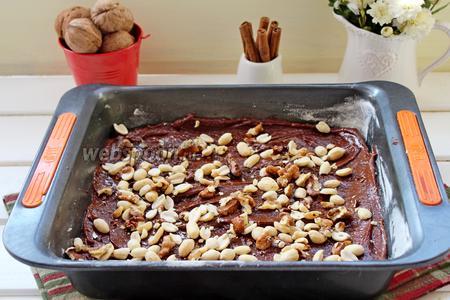 Выложить ровным слоем шоколадное тесто. Присыпать половиной орехов.