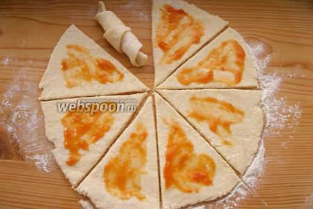 Режем круг на части, как пиццу. Каждый треугольник сворачиваем в виде рогалика. Можно использовать начинку, но необязательно. У меня тут абрикосовое варенье, совсем чуть-чуть (если взять много, то начинка вытечет и подгорит). Но вообще, эти рогалики и без начинки вполне хороши.