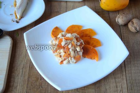 На сервировочную тарелку внахлёст выкладываем полукольца хурмы. Затем аккуратно столовой ложкой выкладываем салат.