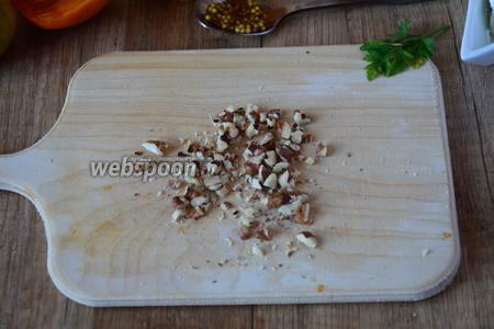 Орехи очищаем и режем ножом на мелкие кусочки.