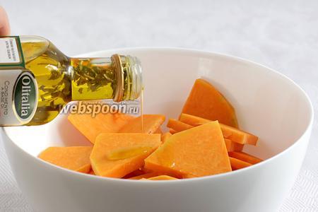 Выложить тыкву в удобную ёмкость и полить оливковым маслом. Хорошенько перемешать. Посыпать морской солью.