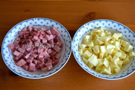 Тем временем включить разогреваться духовку на 180ºC.  Пока обжариваются цукини, нарезать мелкими кубиками вареную ветчину и сыр.