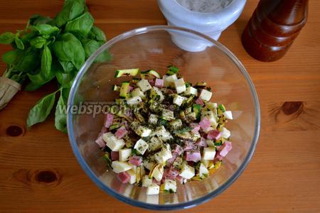 В миску выложить нарезанные ветчину и сыр и цукини. Посолить и поперчить по вкусу, добавить мелко порубленный базилик. Всё перемешать.