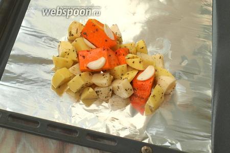 Отрезать 4 куска фольги приблизительно по размеру противеня. Зрительно разделить смесь тыквы и картофеля на 4 порции. Выложить овощи на одну половину листа, зубок чеснока нарезать пластинками и положить сверху.