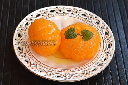 Подавать мандарины охлаждёнными с небольшим количеством сиропа и шариком мороженого. Перед подачей украсить мандарины мелиссой или мятой.
