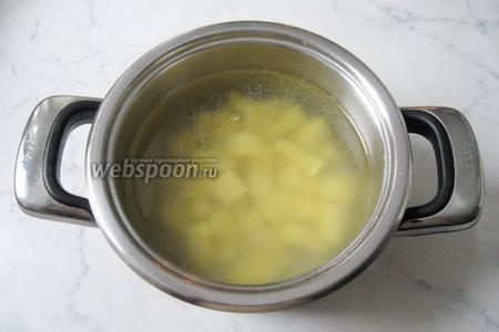 В кастрюлю с рыбным бульоном кладём нарезанный картофель и начинаем варить уху.