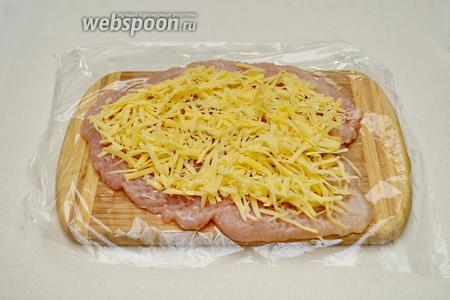 На куриное филе выложить тёртый сыр.