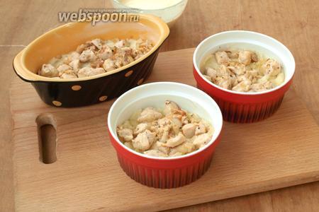 Формы хорошо смазать сливочным маслом. Разложить половину картофельного пюре. Сверху выложить кусочки курицы с луком.