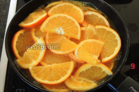 В кипящий сок выкладываем нарезанные апельсины, доводим до закипания и убавим огонь, варим около 5 минут.