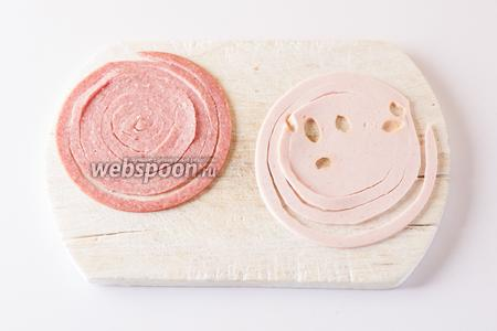Пластины колбасы нарезаем на узкие (0,5-0,7 см) спирали. Это удобнее делать, вращая доску, а не пытаясь вычертить спираль кончиком ножа.