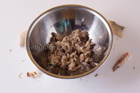 Пока картошка варится, руками растрёпываем копчёную скумбрию «в труху». Тщательно перетираем мясо подушечками пальцев, вычищая мелкие косточки.