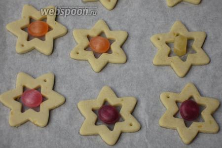 Достать из духовки противень и положить в центр каждой звёздочки леденцовую карамель.