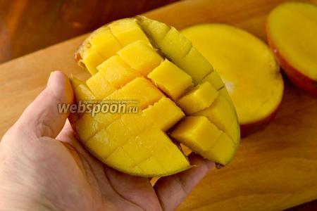 Нанести на отрезанные части манго сетку 1х1, прорезая мякоть, но не повреждая кожицу. Вывернуть кожицу и срезать получившиеся кусочки.