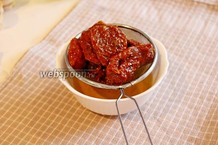 Вяленые томаты опрокинуть на сито и дать стечь маслу. Масло отложить, если не достаточно 100 г, то долить обычное оливковое масло.