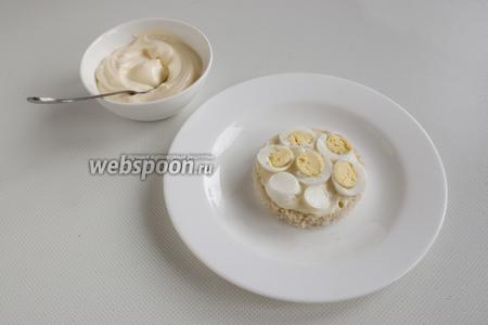 Смажьте первый кружочек майонезом, выложите на тарелку, сверху — ломтики перепелиных яиц.