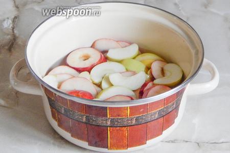 В кастрюлю наливаем воду и засыпаем сахарный песок с лимонной кислотой. Провариваем сироп около 5 минут после закипания. Затем закладываем в горячий сироп яблочные дольки и варим их на самом минимальном огне 5 минут. Оставляем содержимое кастрюли на 3-4 часа до полного остывания. Процедуру (варка-остывание) повторяем 4-5 раз.