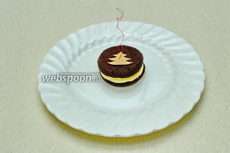 На блюдо или доску выложить печенье. Сверху положить бумажный силуэт.
