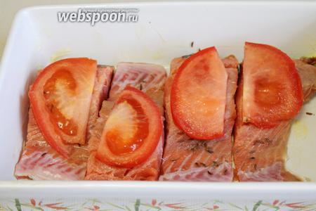 На каждый кусок рыбы уложить дольку помидора.