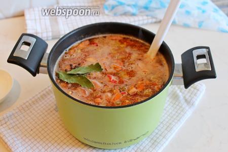 В отварную фасоль добавить обжаренные овощи, обжаренные колбасу и бекон, посолить, добавить перец горошком и лавровый лист, довести до кипения и варить вместе 10 минут.