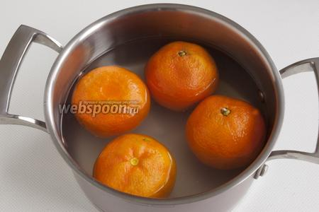 Мандарины промойте, поместите в кастрюлю, залейте полностью водой. С лимона счистите цедру, выдавите сок. Сок добавьте в воду. Варите мандарины 30 минут.