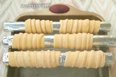 Намотать полоски теста на подготовленые основы внахлёст 4-5 мм, края полосок заправить под низ. Печенье должно выпекаться на весу, поэтому следует подобрать форму, на которую можно будет поместить заготовки.