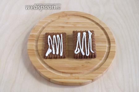 Для каждого домика склейте между собой с помощью глазури по 4 печенья, положив их друг на друга стопочкой.