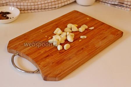 Чеснок нарезать на тонкие дольки, добавить в сковороду, жарить 1 минуту.