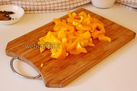 Болгарский перец нарезать на брусочки, добавить в сковороду и жарить вместе 2 минуты.