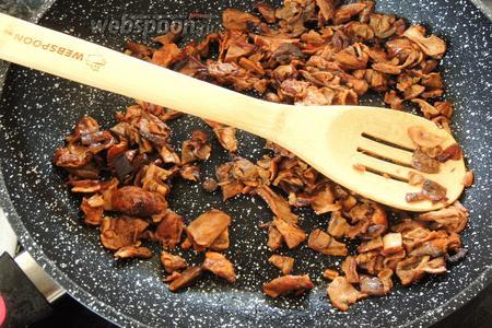 Грибы уже настоялись. Сливаем воду в ёмкость, выжимаем грибы, она нам нужна для соуса. Снова растопим масло и обжарим мелко нарезанные грибы около 2 минут.