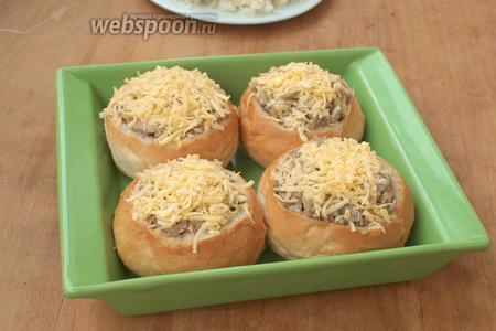 Форму, в которой будут запекаться булочки, смазать маслом, выложить в неё булочки, посыпать сверху натёртым сыром немного прижимая.