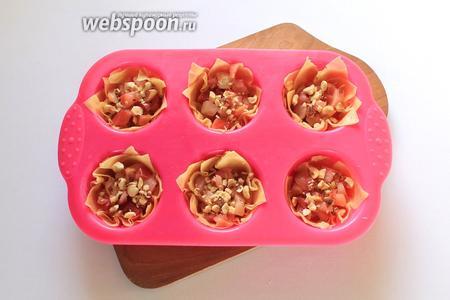 На дно каждой корзиночки выложить яблочную начинку и посыпать измельчёнными обжаренными орехами.