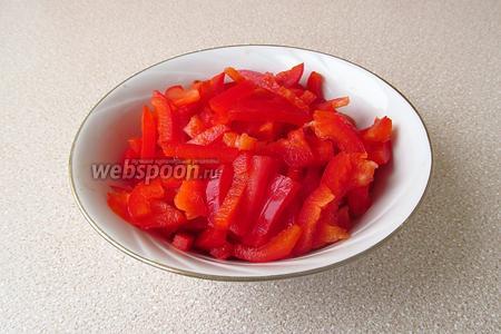 Плод сладкого перца вымыть, разрезать вдоль на 4 части, удалить плодоножку и семеносцы с семенами, а затем каждую четвертинку тонко нашинковать поперёк.