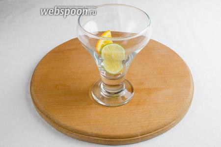 В термобокал положить половину дольки апельсина и дольку лайма.