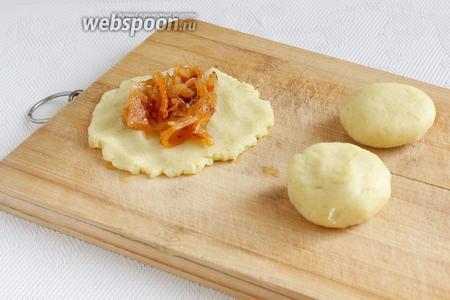 Каждый колобок расплющить и положить внутрь капустную начинку.