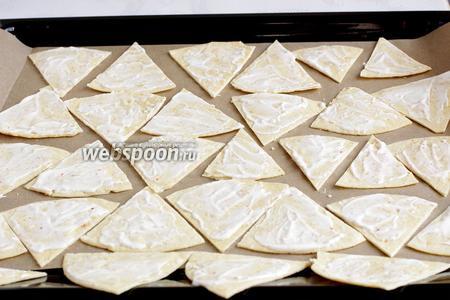 Сегменты из лепёшки выложить на противень и смазать полученным сметанным соусом.