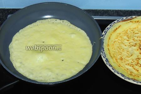 Смазываем каждый раз горячую сковороду с антипригарным покрытием кусочком масла. Наливаем сразу тесто в сковороду, толщиной около 1-2 мм, дадим тесту растечься по всему дну и выпекаем несколько секунд, как только тесто будет само отлипать от дна, можно его переворачивать на другую сторону. И ещё несколько секунд выпекаем. Складываем омлетики на горячую тарелку и накрываем, чтобы не остывали.