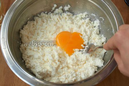 Затем в творог добавить 1 куриный желток и хорошо перемешать.