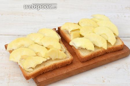 На сыр уложить плотно тонкие ломтики очищенного яблока.