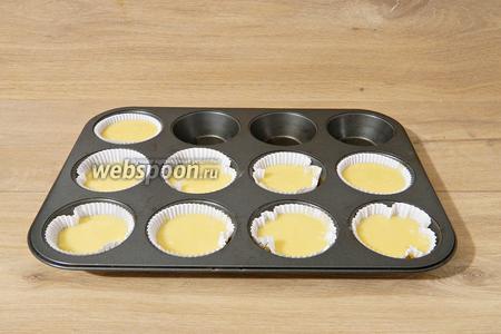 В форму для выпечки кексов раскладываем бумажные формочки. Если их нет, то форму смазываем сливочным маслом и посыпаем манкой, мукой или кокосовой стружкой. По формочкам разливаем тесто.