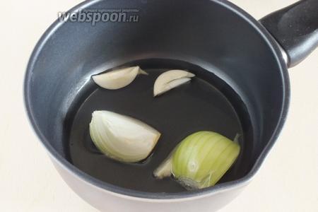 Нагрейте в ковше масло, добавьте крупно нарезанные лук и чеснок. Обжарьте до золотистого цвета, а затем удалите из масла.