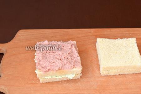 Накрыть вторым куском хлеба и смазать его колбасной начинкой.