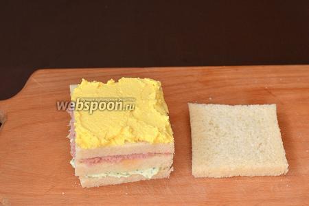 Накрыть третьим куском хлеба и смазать яичной начинкой. Накрыть четвёртым куском хлеба и немного прижать сверху.