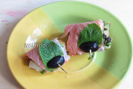 Свернуть в рулетик и проткнуть зубочисткой. Украсить маслинами и листиком мяты. Закуска из двух видов рыбы готова. Подавать сразу или затянуть плёнкой и оставить до подачи до 6 часов. Приятного аппетита!