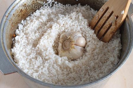 Сверху выложите промытый рис. В серединку вкопайте очищенную от верхних чешуек и промытую головку чеснока.