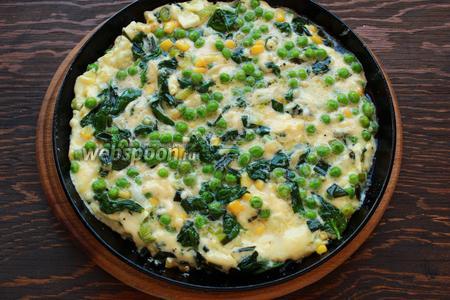 Залить яйцами и как только схватится по бокам, отправить в разогретую до 180 °C духовку на 7-10 минут.