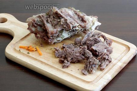 Отваренное мясо достать из бульона, нарезать на кусочки, освобождая от кости. Вернуть кусочки мяса в бульон.