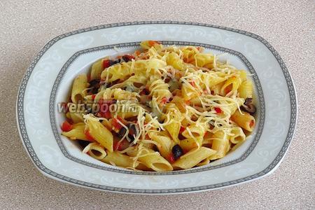 Выложить макаронные изделия с соусом на блюдо горкой и посыпать тёртым сыром.