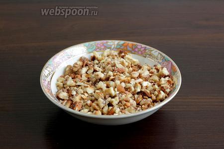 Грецкие орехи и косточки абрикос поджарить, а затем измельчить на средние кусочки. Я поместила орехи в пакет и побила их скалкой.